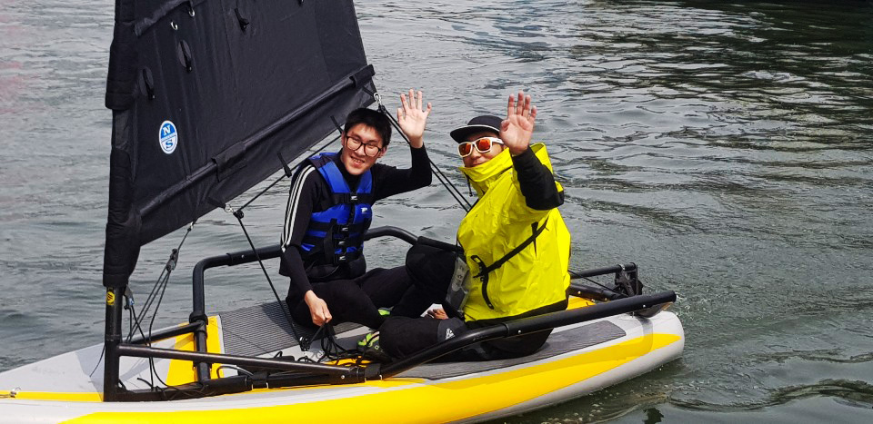 Adults trying Tiwal 3 inflatable sailboat in South Korea